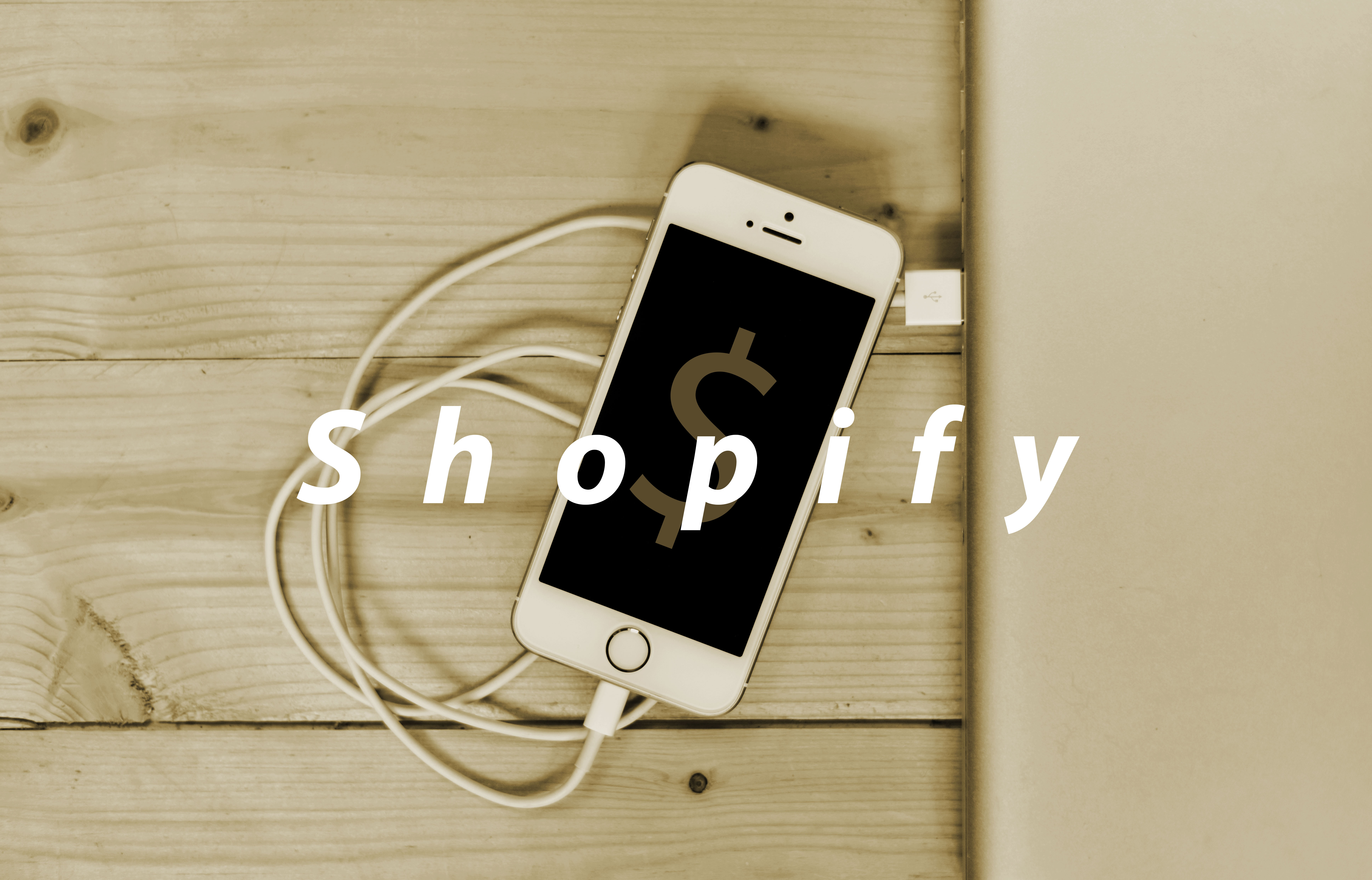 Iphone Plugged Into The Wall With Shopify Text Overlaid Over The Image.