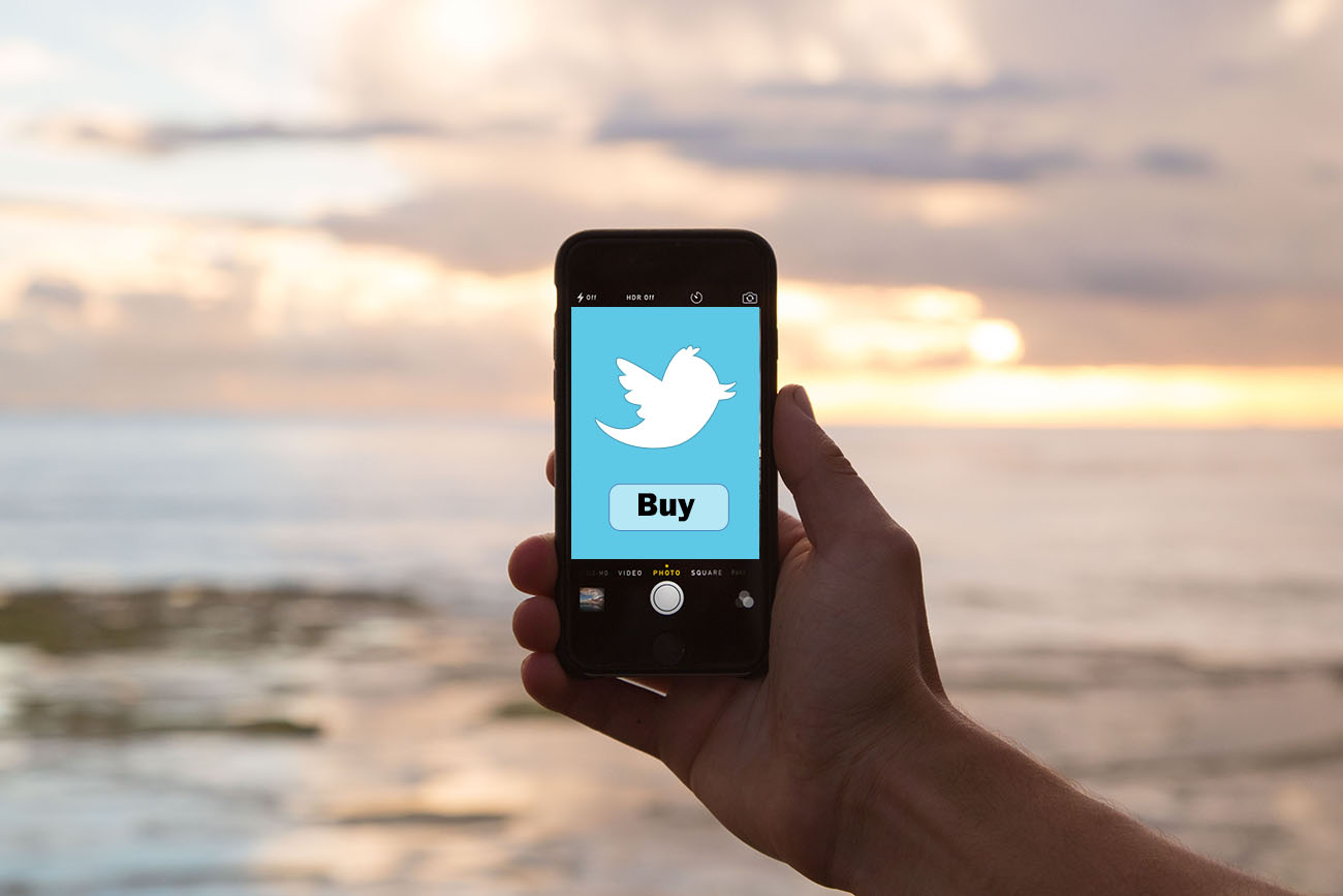 Mobile Phone Showing A Twitter Bird Icon With A Buy Button Below It.