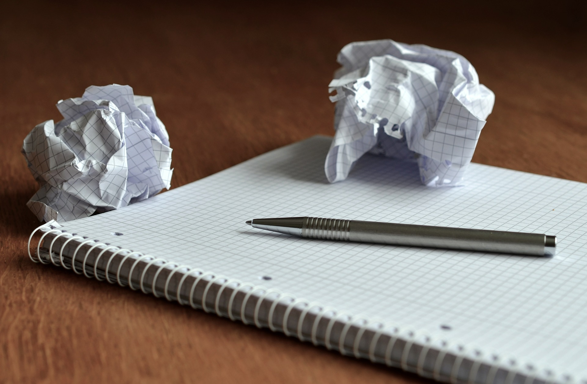 A Notebook With Two Crumpled Balls Of Paper On Top.