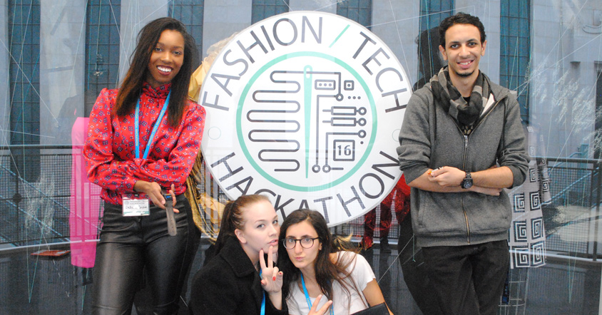 Three Women And A Man In Front Of A SIgn For Fashion and Tech Hackathon.