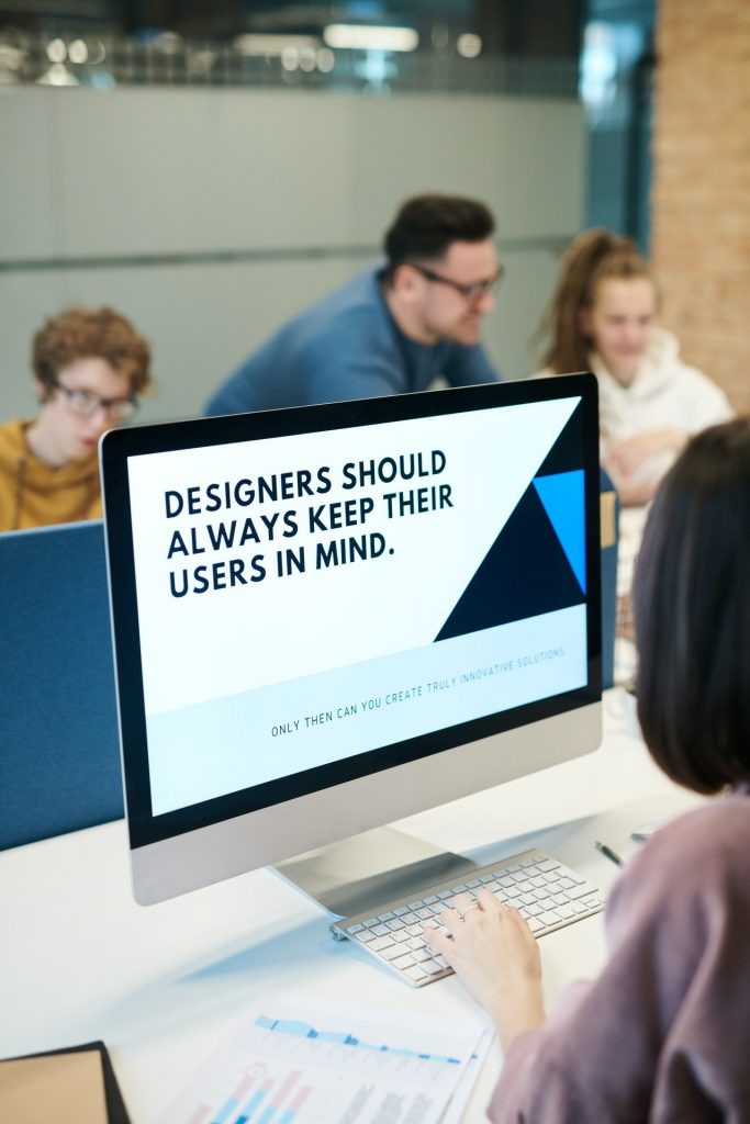 "Room of people with one person looking at a laptop. The laptop screen reads ""Designers should always keep their users in mind."""